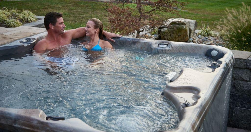 Man and Woman in Hot Tub Backyard