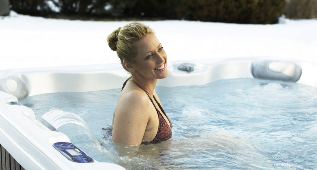 woman enjoying soaking in a hot tub from Aspen Spas